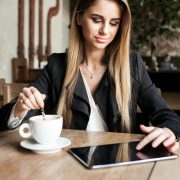 A woman sitting at a table with a cup of coffee