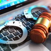 Handcuffs and judge mallet on laptop keyboard